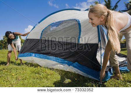 Hispanic women setting up tent
