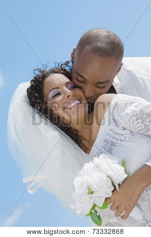 Multi-ethnic bride and groom hugging