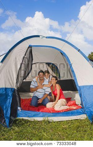 Hispanic family sitting in tent
