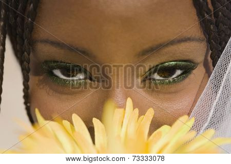 African woman with flower in front of face