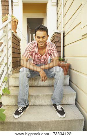 Indian man sitting on steps