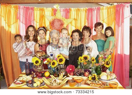 Multi-ethnic Mixed Race female family members behind buffet table