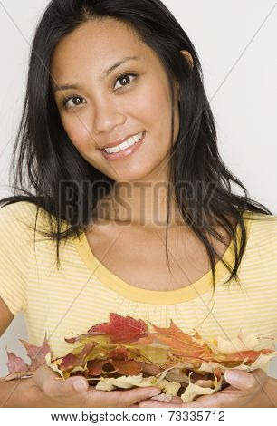 Pacific Islander woman holding autumn leaves