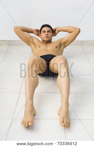 Bare-chested Hispanic man doing sit-ups