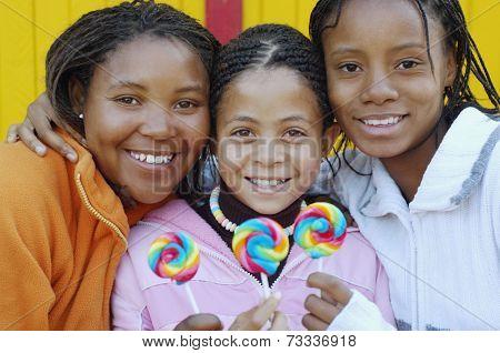 Multi-ethnic girls holding lollipops