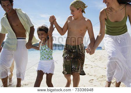 Hispanic family holding hands at beach