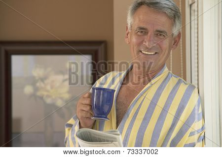 Hispanic man holding coffee and newspaper
