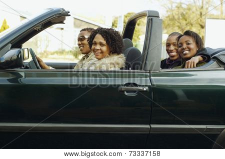 African couples driving in convertible car