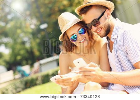A picture of a happy couple with smartphones in the park