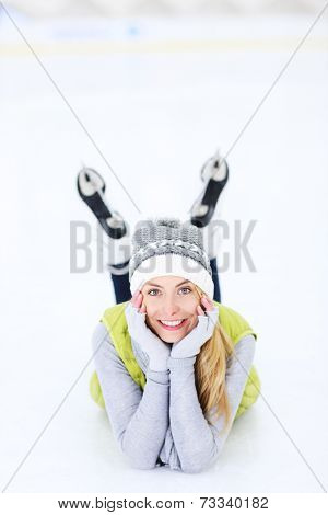 A picture of a happy woman lying on the ice rink