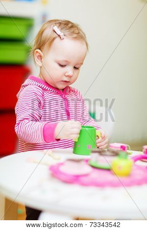 Adorable toddler girl playing with toys at home or daycare place