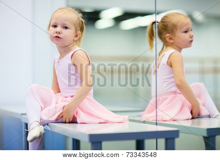 Adorable little ballerina wearing pink leotard in dancing school