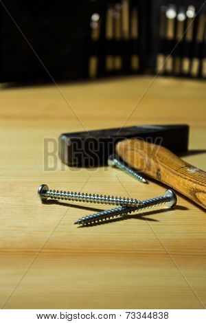 Screws And Hammer On A Table