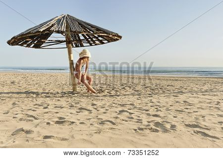 Young attractive girl on beach in bikini applying sunscreen