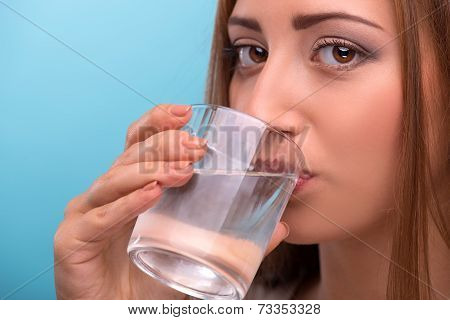 Portrait of young beautiful girl drinking clean water from a gla