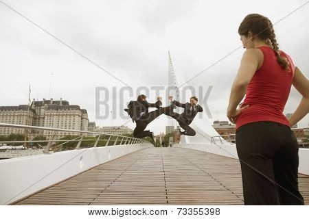 Multi-ethnic businessmen fighting next to woman