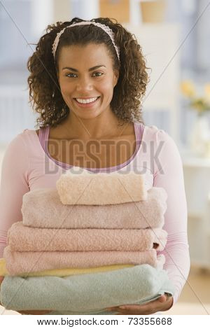 African woman carrying stack of towels