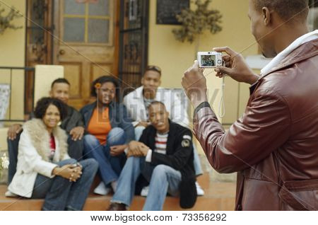 African man taking photograph of friends