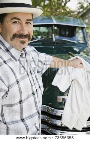 Hispanic man waxing truck