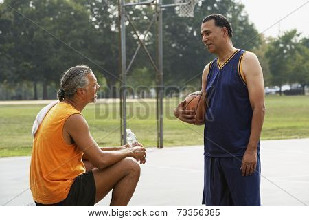 African men talking on basketball court