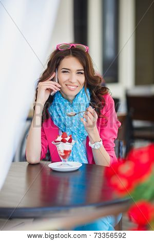 The young woman, eats a dessert and speaks by the mobile phone