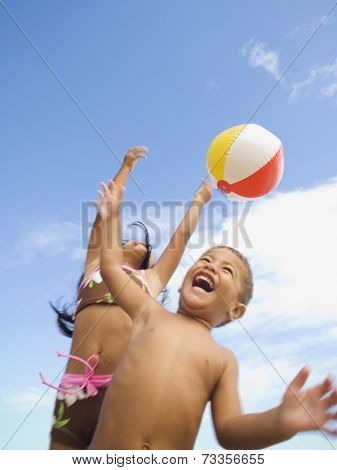 Pacific Islander siblings playing with beach ball