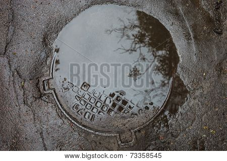 The Puddle On The Manhole In Asphalt Surface
