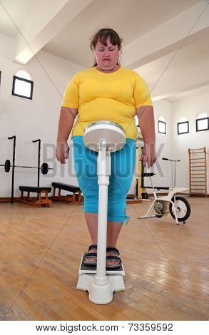 women with overweight standing on scales in the gym