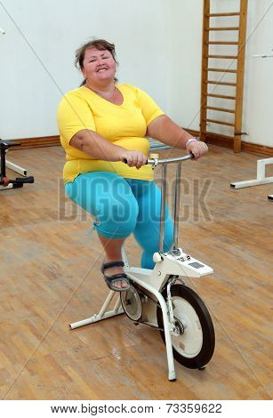 smiling overweight woman exercising on bike simulator