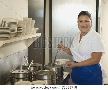 Hispanic waitress ladling soup