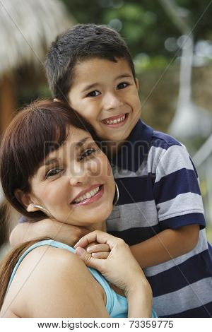 Hispanic mother and son hugging