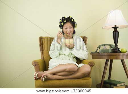 Asian woman in curlers eating cereal