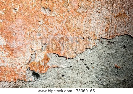 Concrete Surface With The Remains Of Orange Paint And Whitewash And Partly Fallen Plaster