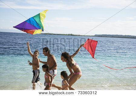 Hispanic family flying kites at beach