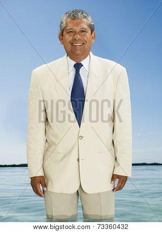 Hispanic businessman standing in water