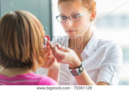 Optometry concept - pretty, young female optometrist examining her patient's eyes, finding the optimal correction to achieve optimal sight