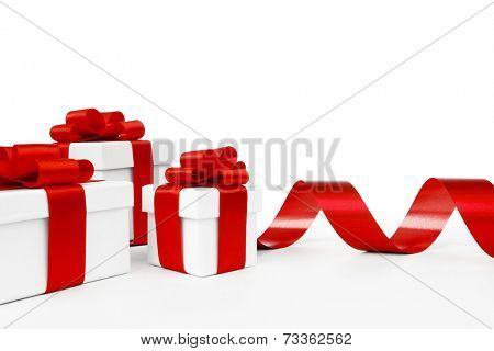 White gift boxes tied with a red satin ribbon bow isolated on white background