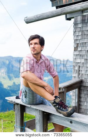 Hiking - Young man sitting at mountain hut in the Bavarian Alps and enjoys the panorama in the leisure time or in vacation