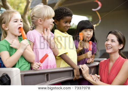 Group of young preschool children playing in daycare with teacher