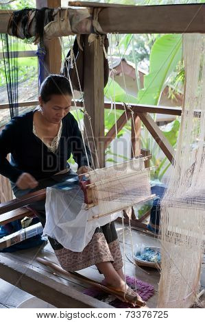 Woman Weaving Silk In Traditional Way At Manual Loom. Laos