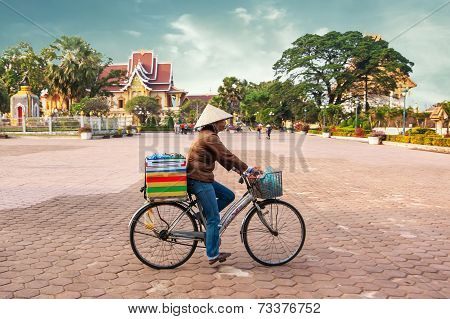 Local Woman On Bicycle Selling Food At City Square. Vientiane, Laos
