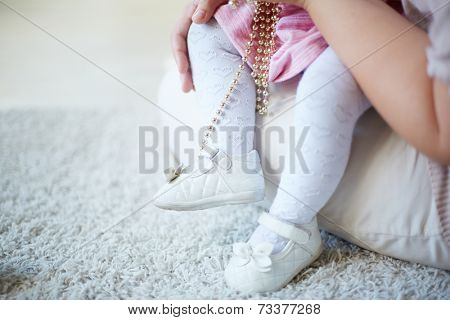 Legs of a toddler sitting on her mother�?�¢??s laps