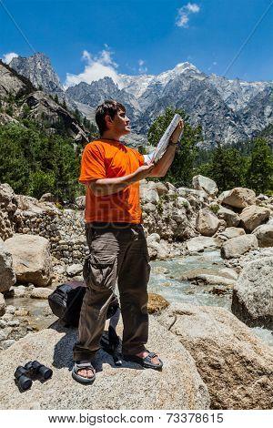 Hiker trekker studying map route on trek in Himalayas mountains. Himachal Pradesh,India