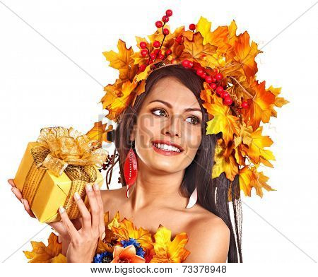 Girl with wreath of autumn leaves holding basket with fruit.