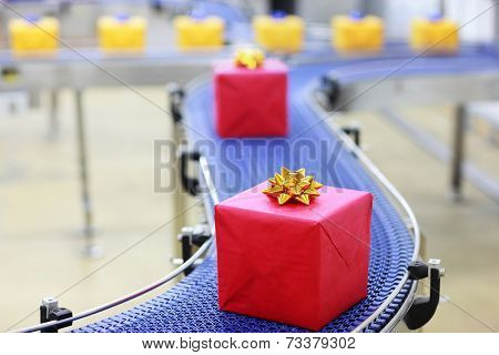 presents in boxes on conveyor belt in Christmas gifts factory