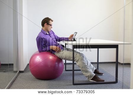 young man on stability ball working with tablet in office  - relaxed position at workstation -