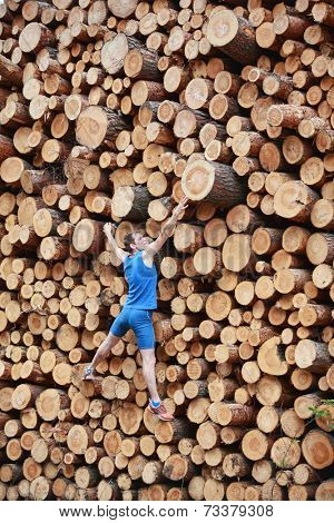 Fit,young man climbing the large pile of cut wooden logs - back view
