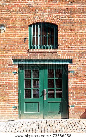 Green Door And Window In Brick Wall