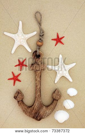 Starfish and cockle shells with decorative anchor on beach sand background.