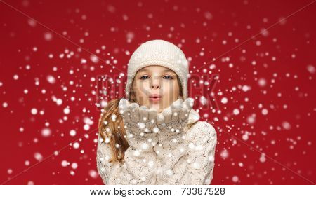 christmas, xmas and happiness concept - happy girl in winter clothes blowing on palms